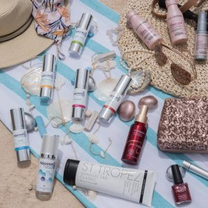 Flat lay photography of cosmetic products on a beach towel with sunhats